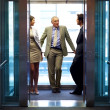 Successful business standing in office elevator - Foto Stock