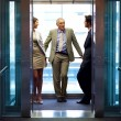 Successful business standing in office elevator - Foto de Stock