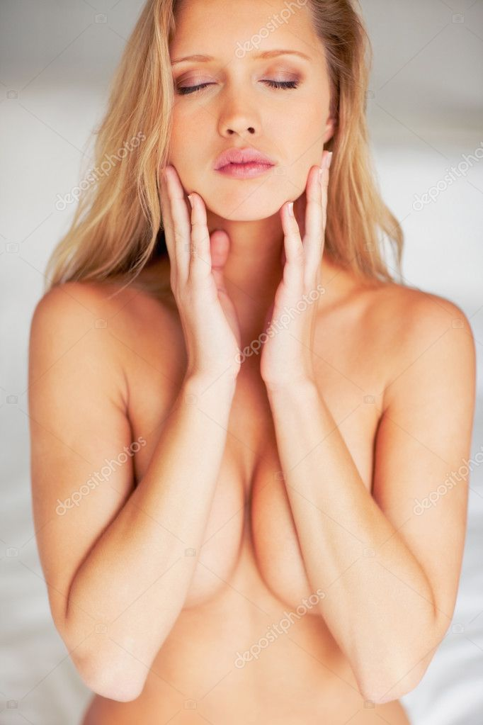 Portrait of a sexy young naked model covering her breast with eyes closed