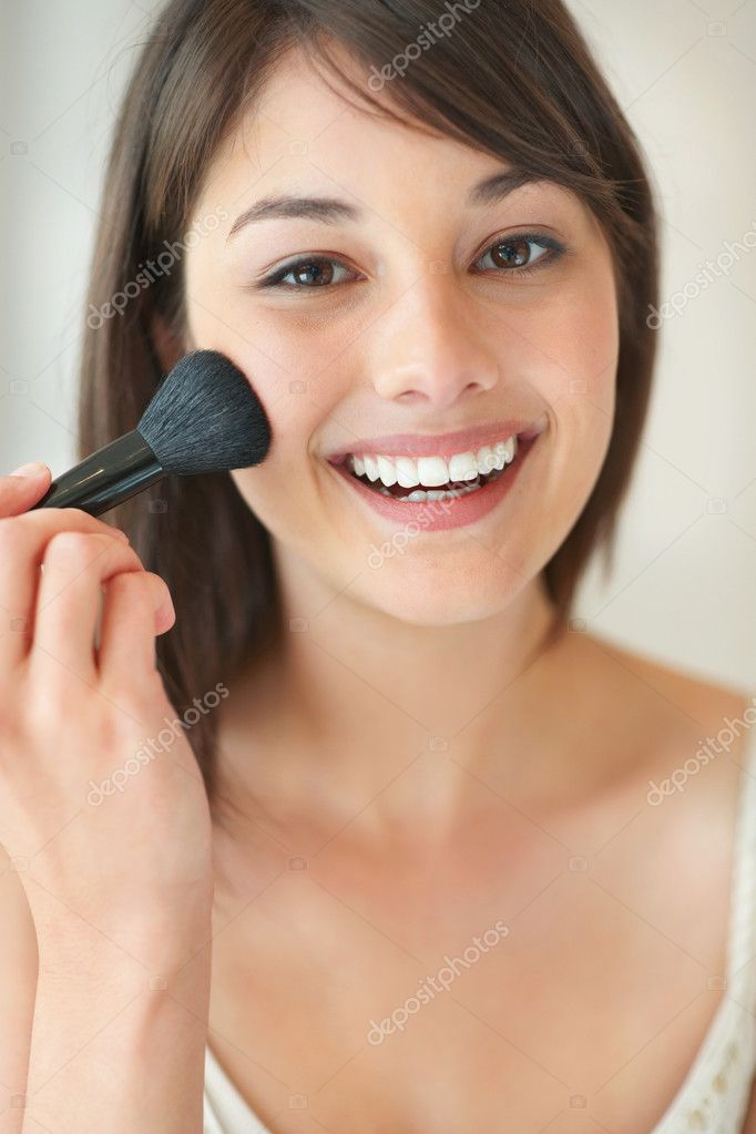 Portrait of an attractive young lady applying blusher on her face — Stock Photo #3462149