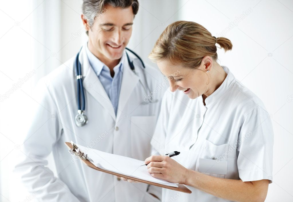Happy middle aged hospital staff making notes together — Stock Photo #3462897
