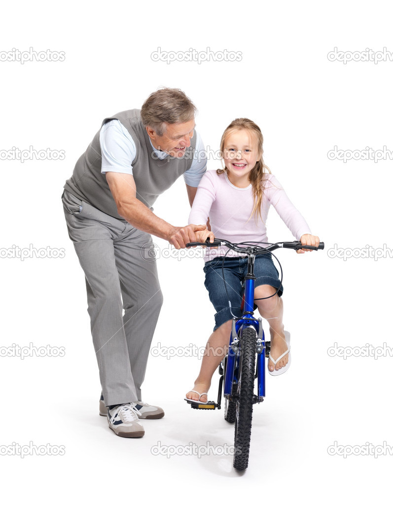 Portrait of a old man helping his granddaughter to ride a bicycle on white background — Stock Photo #3462951
