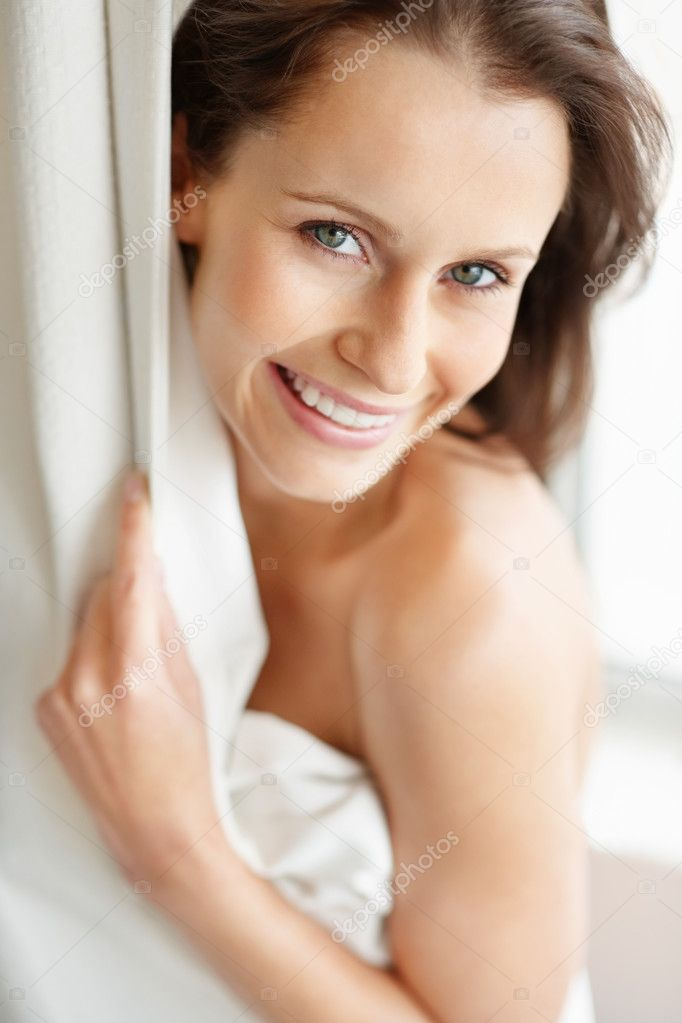 Closeup portrait of a cheerful young female hiding behind a curtain — Stock Photo #3464269