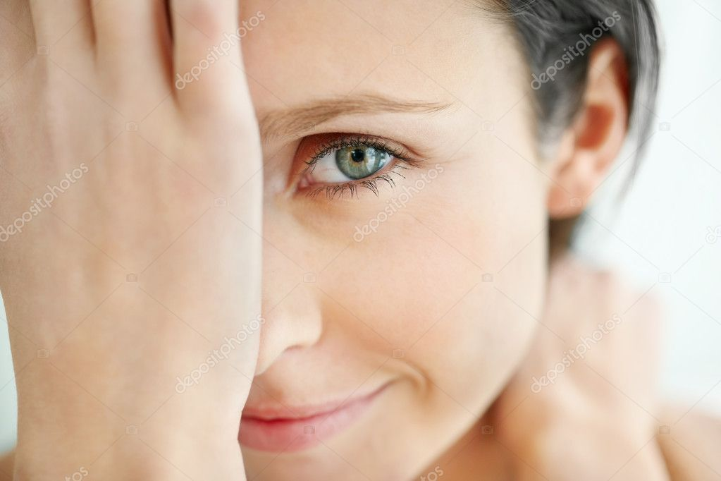 Closeup of a smiling female covering one eye  Stock Photo #3464407