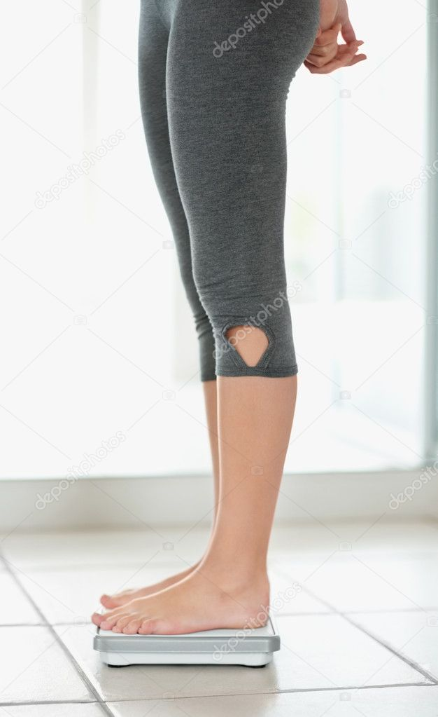 Side view low section of a female standing on a weighing scale — Stock Photo #3464471