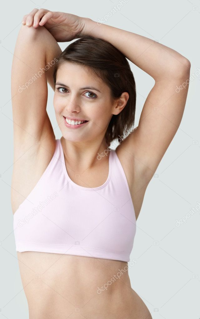 Portrait of a toned young female stretching her hands against white  Stock Photo #3464502