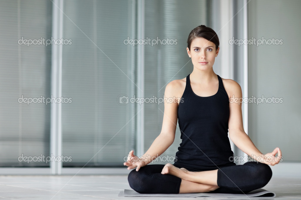 Lotus position - Portrait of a cute young female practicing yoga on a mat — Lizenzfreies Foto #3464595