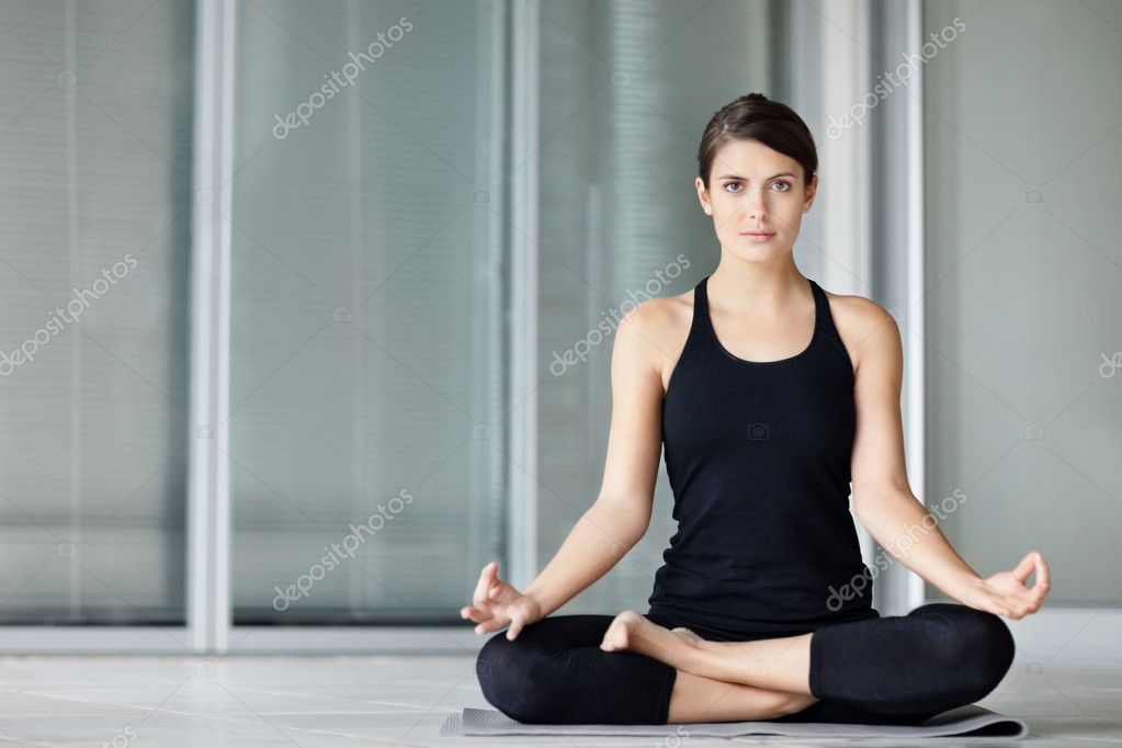 Lotus position - Portrait of a cute young female practicing yoga on a mat — Foto de Stock   #3464595