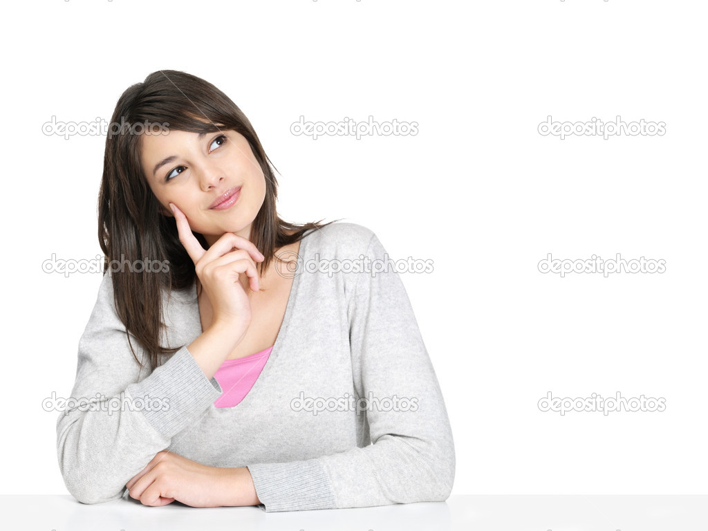 Portrait of a young casual woman sitting at a table against white and lost in thought — Stock Photo #3465290
