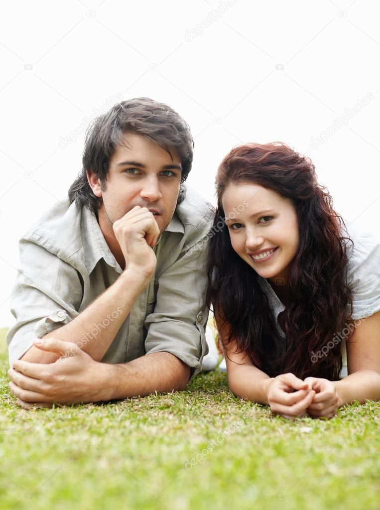 Happy young couple lying side by side on a grass lawn — Stock Photo #3466733