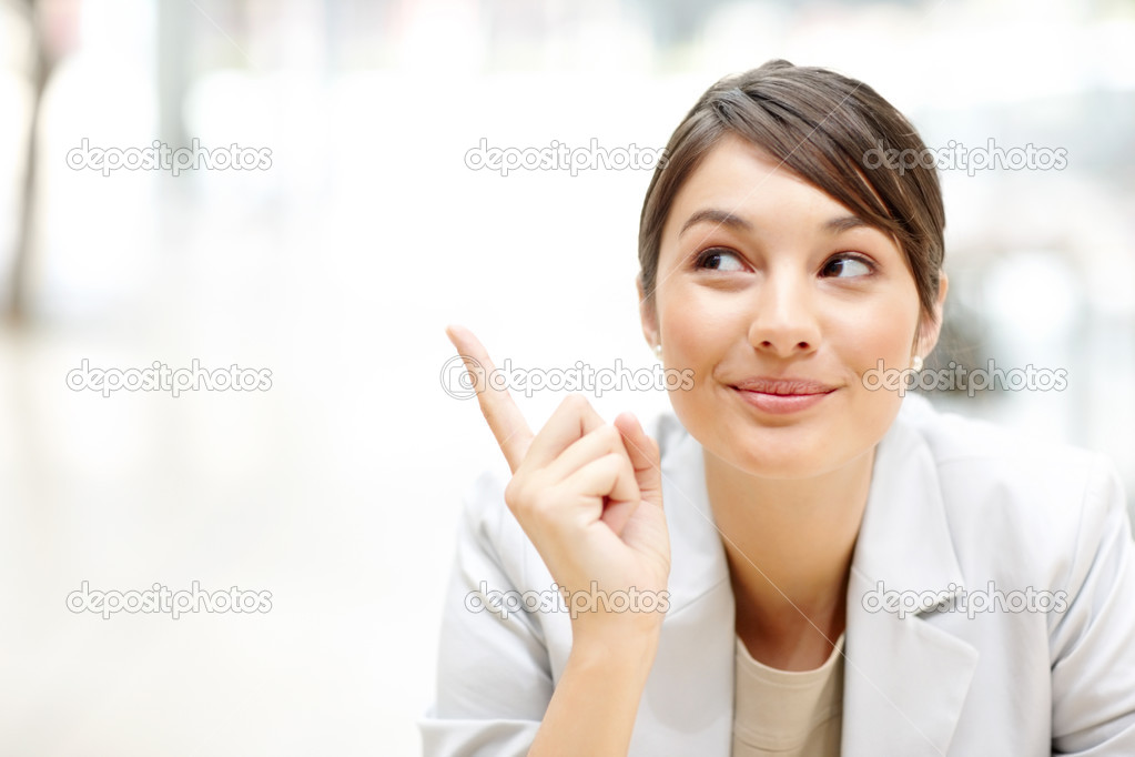 Portrait of cute young female business executive looking and pointing at copyspace — Stock Photo #3467237