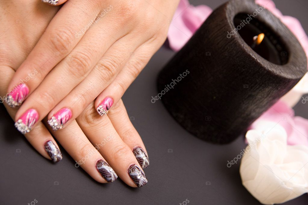 Manicure, nail polisher arranged with flowers and candle  Stock Photo #2702356