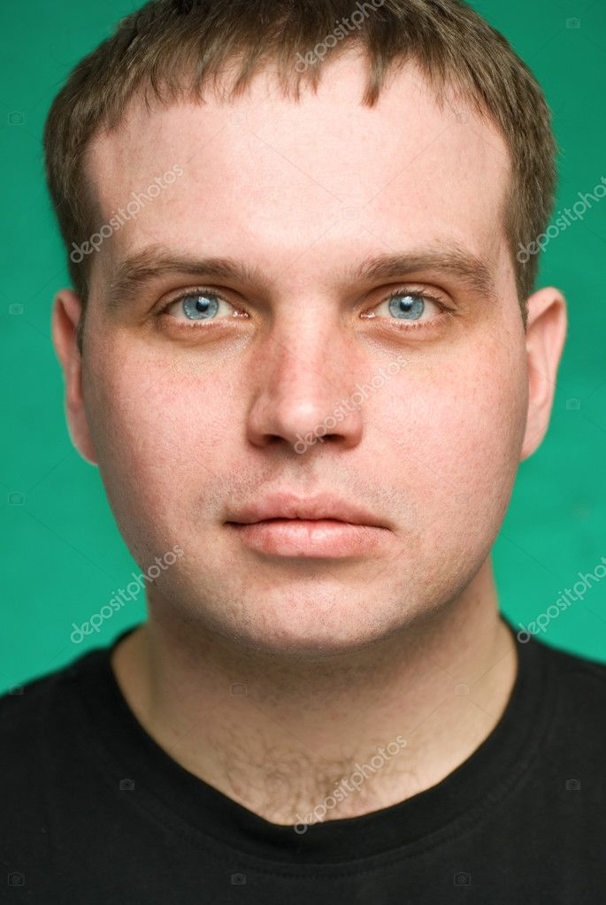 Portrait of the serious young man on green background. Focus on eyes, small depth of feild. — Stock Photo #2781923