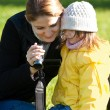 Motehr and daughter view a video recording on the camcorder — Stockfoto