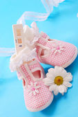 Pregnancy test and baby shoes — Stock fotografie