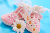 Pregnancy test and baby shoes — Zdjęcie stockowe