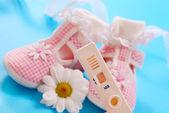 Test di gravidanza e scarpe bambino — Foto Stock