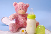 Bottle of milk for baby and teddy bear — Stok fotoğraf
