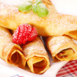 Rolled pancakes with icing sugar — Stock Photo