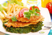 Fish on spinach with fries — Stock Photo