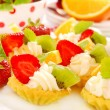 Mini tartlets with whipped cream and fruits — Stock Photo
