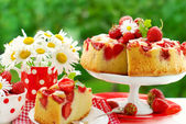Strawberry cake on table in the garden — Stock Photo