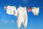 Baby clothes on clothesline — Stock Photo