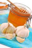 Garlic and jar of honey — Stock Photo