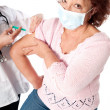 Senior woman getting flu vaccine — Stock Photo