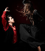 Young couple passion flamenco dancing on red lig — Stock Photo