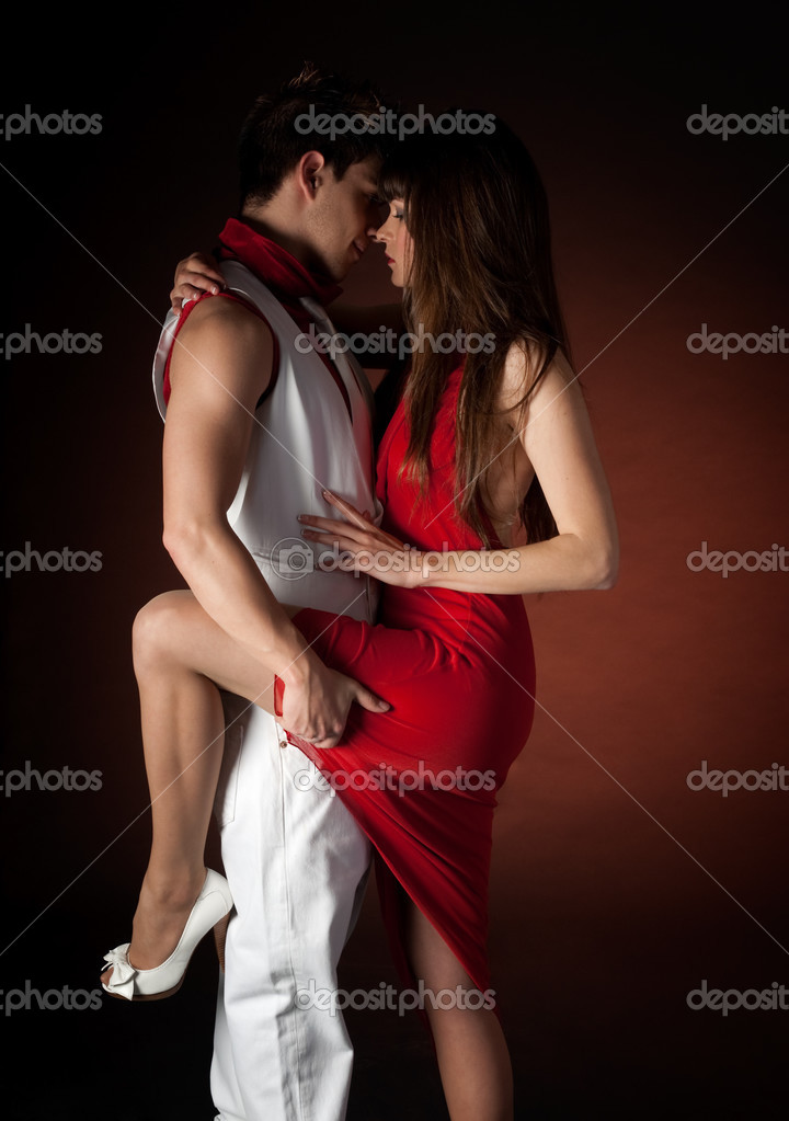Young couple dancing embrace passion romance on dark red light background.  — Photo #3205029