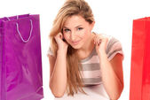 Young woman with shopping bags lying on floor on white background — Stock Photo