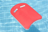 A red float floating in blue pool — Stock Photo