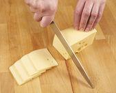 Kobieta cięcia sera przez nóż — Zdjęcie stockowe