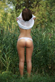 The beautiful girl undresses on the nature — Stock Photo