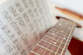 An acoustic guitar with a book of chords — Stock Photo