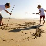kinderen schrijven in zand — Stockfoto