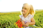 Adorable Girl outside with flowers — Stock Photo