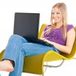 Woman on chair with laptop — Stock Photo