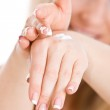 Woman creaming hands — Stock Photo