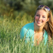 Blonde girl in grass — Stock Photo