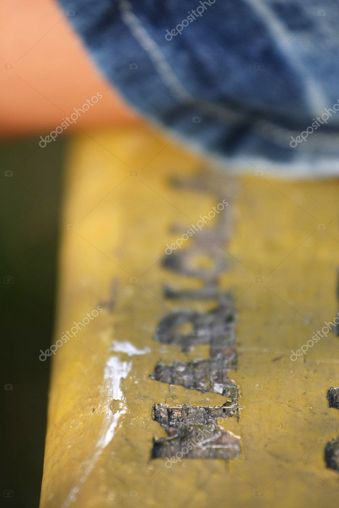 Lone woman on a bench with carved letters — Stock Photo #2811622