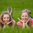 Stock Photo: Sisters lay on the grass