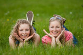 Sisters lay on the grass — Stock Photo