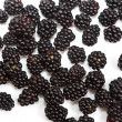 Composition of ripe black and red raspberries and strawberries - Stock Photo
