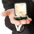 Man in suit holding engagement ring on white isolated background — Stock Photo