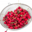 Cherry in colander over white — Stock Photo