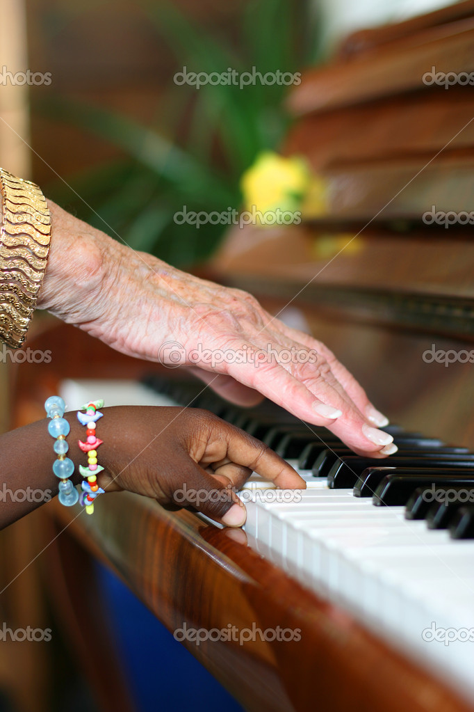 One older white hand and one younger black hand playing the piano — Stock Photo #2902845