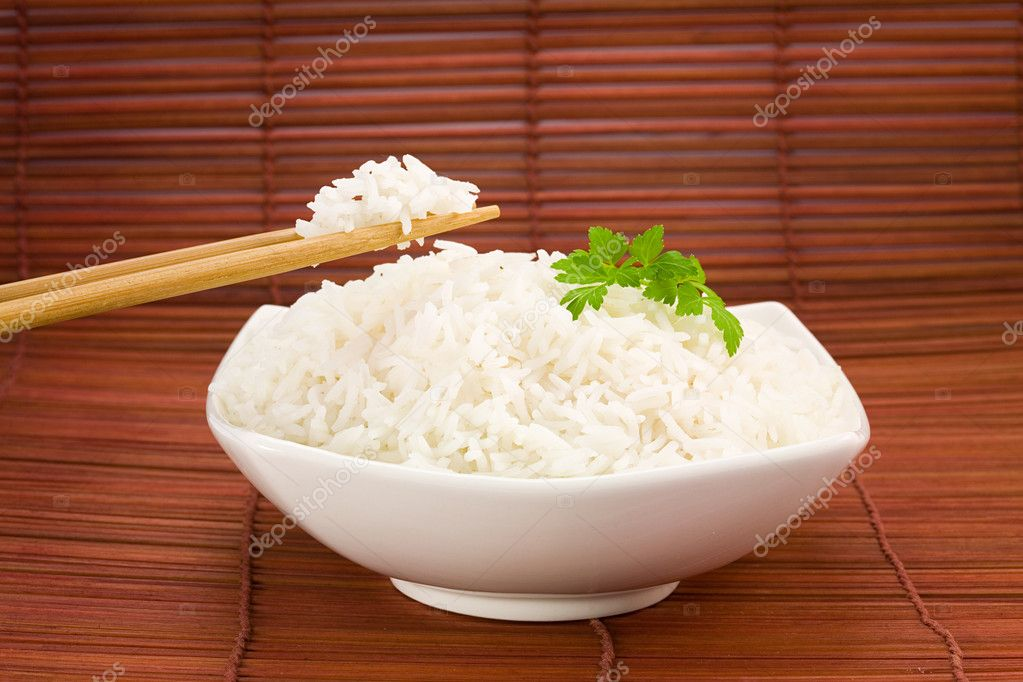 Closeup of rice on chopsticks and a bowl on mat — Photo #2911583