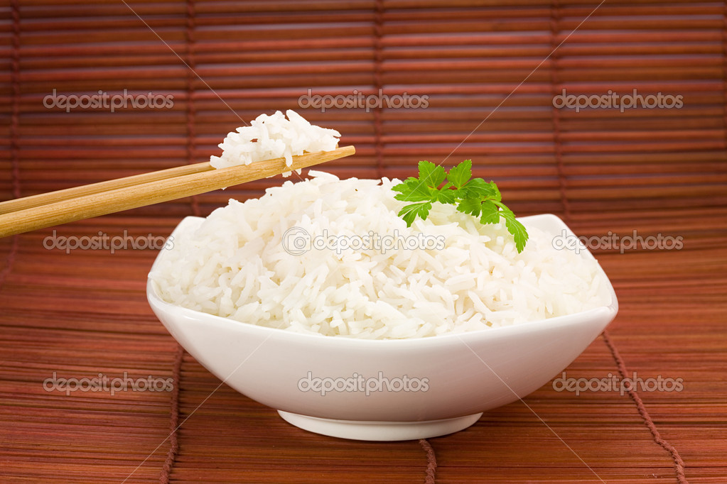 Closeup of rice on chopsticks and a bowl on mat   #2911583
